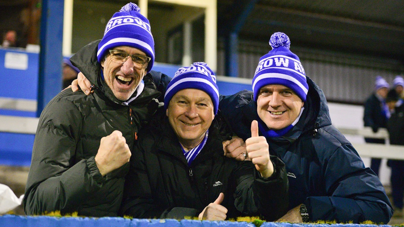A photo of three Barrow fans celebrating