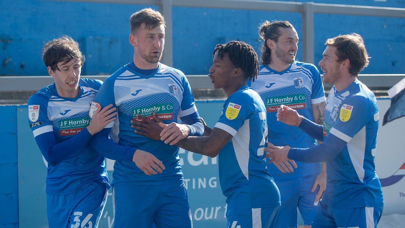 A photograph of the Barrow players celebrating Scott Quigley's equaliser against Newport